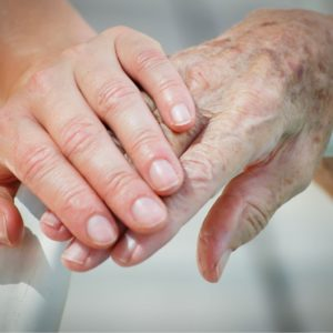 Nurse holds the hand of elderly assisted living resident.