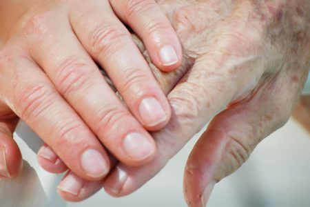 Nurse holds the hand of elderly assisted living resident.