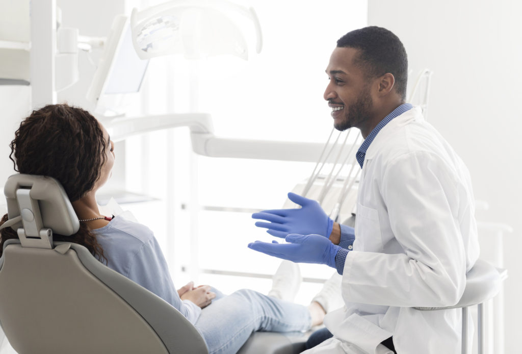 Friendly black dentist explaining patient treatment plan