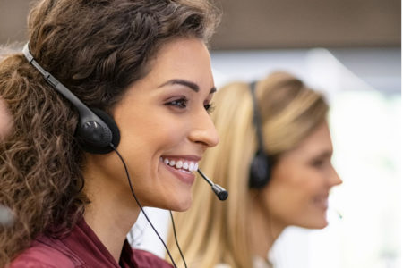 Two women answer phone calls for healthcare providers.