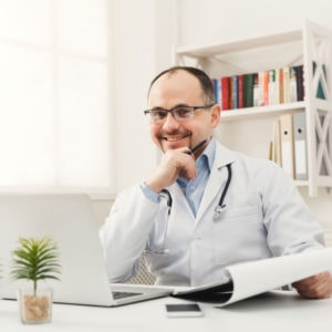 A doctor works on a computer from his home office.