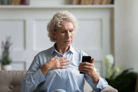 An older patient is worried about a text message on her phone.