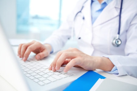 A doctor looks at patient data on a computer.