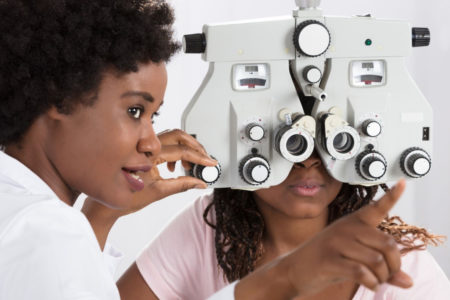 female optometrist performs eye exam on patient