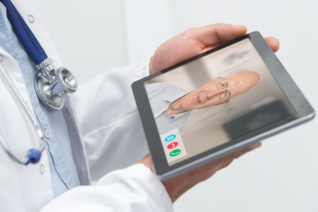 A doctor cares for a elderly patient in an assisted living facility via telemedicine.